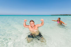 Muchacho y niña de Tenage que relajan, nadando y disfrutando allí del tiempo libre en el océano Fotografía de archivo libre de regalías