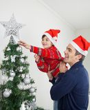 Muchacho y padre Decorating Christmas Tree Fotos de archivo