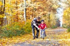 Muchacho y padre del niño con la bicicleta en bosque del otoño Imagen de archivo libre de regalías