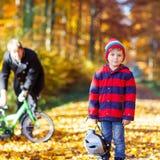 Muchacho y padre del niño con la bicicleta en bosque del otoño Foto de archivo
