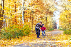 Muchacho y padre del niño con la bicicleta en otoño Imágenes de archivo libres de regalías
