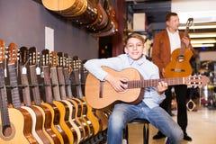 Muchacho y padre que eligen la guitarra acústica Fotografía de archivo