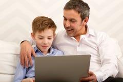 Muchacho y padre que usa el ordenador portátil junto Fotos de archivo