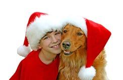 Muchacho y perro en sombreros de la Navidad imagenes de archivo