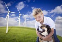 Muchacho y perro jovenes en campo de la turbina de viento Foto de archivo