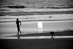 Muchacho y perro que se ejecutan hacia el agua Imagen de archivo