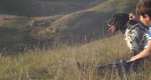 Muchacho y perro que se sientan en la ladera en la puesta del sol y que miran la puesta del sol almacen de metraje de vídeo