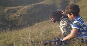 Muchacho y perro que se sientan en la ladera en la puesta del sol y que miran la puesta del sol metrajes