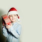 Muchacho y regalo del niño de la Navidad ¿Cuál está en la caja de regalo? Fotografía de archivo