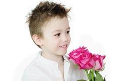 Muchacho y rosas Imagen de archivo