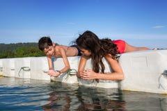 Muchacho y su hermana que cogen las gambas minúsculas mientras que estaban en la plataforma flotante en la isla tropical fotografía de archivo libre de regalías