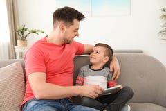 Muchacho y su padre con la tableta que se sienta en el sof? Tiempo de la familia imágenes de archivo libres de regalías