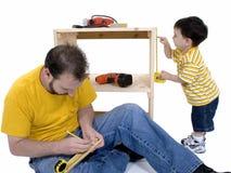 Muchacho y su padre que construyen una cabina de almacenaje junto Fotos de archivo libres de regalías