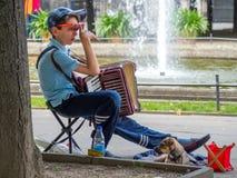 Muchacho y su perro con una armónica en el parque Foto de archivo libre de regalías