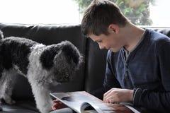 Muchacho y su perro de caniche que miran el álbum de foto imagen de archivo libre de regalías