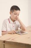 Muchacho y tableta Agujereado con la tableta Aprenda y juegue Fotos de archivo