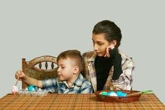 Muchacho y una más vieja hermana que colorean los huevos de Pascua Fotografía de archivo
