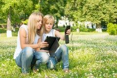 Muchacho y una muchacha con una tableta y un teléfono digitales Fotografía de archivo libre de regalías
