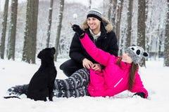 Muchacho y una muchacha que juega con el perro Fotos de archivo