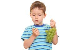 Muchacho y uvas Foto de archivo
