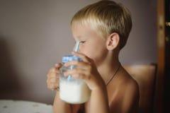 Muchacho y vidrio de leche imagenes de archivo