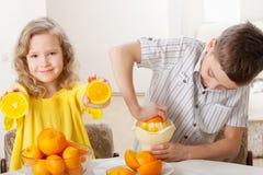 Muchacho y zumo de naranja exprimido muchacha Foto de archivo
