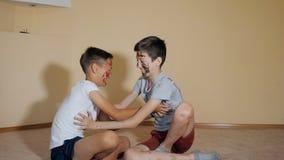 Muchachos adolescentes con las manos y las caras en las pinturas coloridas que se sientan en juego del piso con uno a almacen de video