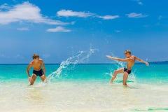 Muchachos adolescentes felices que se divierten en la playa tropical Vacatio del verano Foto de archivo libre de regalías