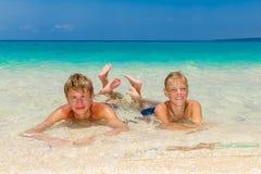 Muchachos adolescentes felices que se relajan en la playa Mar tropical en el backg Foto de archivo libre de regalías