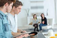 Muchachos adolescentes jovenes felices del retrato que cocinan para sus novias Fotografía de archivo