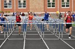 Muchachos adolescentes que compiten en carrera de vallas de la High School secundaria Foto de archivo libre de regalías