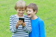 Muchachos con el teléfono móvil Niños que sonríen, mirando a la pantalla, jugando a juegos o usando el uso outdoor tecnología Fotos de archivo libres de regalías
