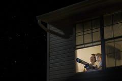 Muchachos con el telescopio que mira el cielo nocturno Foto de archivo