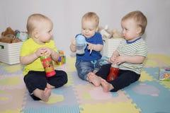 3 muchachos con las botellas de agua del bebé Imagen de archivo libre de regalías