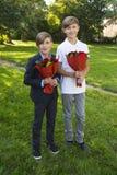 Muchachos con los ramos de rosas en el día del ` s de la madre Fotos de archivo