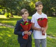 Muchachos con los ramos de rosas en el día del ` s de la madre Foto de archivo libre de regalías