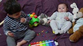 Muchachos de dos años y de 4 meses que juegan en lecho del purrple con el xilófono y los juguetes suaves metrajes