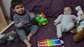 Muchachos de dos años y de 4 meses que juegan en lecho del purrple con el xilófono y los juguetes suaves almacen de metraje de vídeo