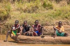 Muchachos de Giriama que se sientan en la canoa de cobertizo Foto de archivo