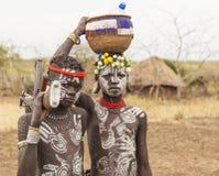 Muchachos de la tribu de Mursi con la ametralladora en el pueblo de Mirobey Omo V Fotografía de archivo libre de regalías
