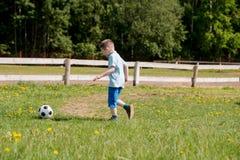 Muchachos de los adolescentes que juegan el partido de fútbol del fútbol Futbolistas jovenes que corren y que golpean el balón de Foto de archivo