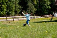 Muchachos de los adolescentes que juegan el partido de fútbol del fútbol Futbolistas jovenes que corren y que golpean el balón de Imagen de archivo