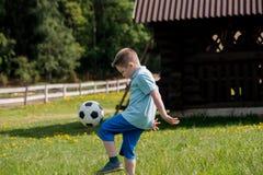 Muchachos de los adolescentes que juegan el partido de fútbol del fútbol Futbolistas jovenes que corren y que golpean el balón de Fotos de archivo