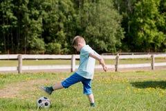 Muchachos de los adolescentes que juegan el partido de fútbol del fútbol Futbolistas jovenes que corren y que golpean el balón de Imágenes de archivo libres de regalías