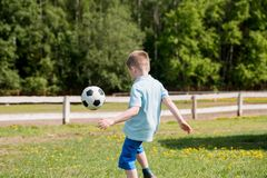 Muchachos de los adolescentes que juegan el partido de fútbol del fútbol Futbolistas jovenes que corren y que golpean el balón de Imagenes de archivo