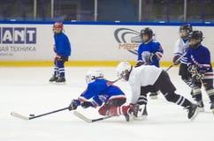 Muchachos de los niños que juegan a hockey en el hielo en el estadio de Yunost foto de archivo libre de regalías