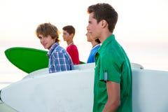 Muchachos del adolescente de la persona que practica surf que caminan en la orilla de la playa Foto de archivo