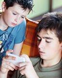 Muchachos del adolescente que juegan en el smartphone, al aire libre Imagen de archivo