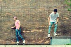 Muchachos del skater por la pared de ladrillo Imagen de archivo
