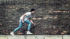 Muchachos del skater por la pared de ladrillo Fotos de archivo